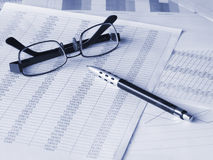 Glasses and pen on financial documents. Toned blue. Shallow DOF Stock Images