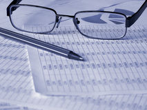 Glasses and pen on financial documents. Toned blue. Shallow DOF Stock Photos