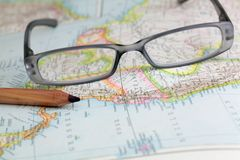 Glasses. And a pen on a historical map stock images