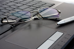 Glasses and pen on laptop royalty free stock images