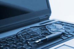 Glasses and pen on laptop Royalty Free Stock Photo