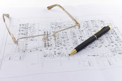 Glasses and pen lie on the engineering drawing. On white background Stock Photo