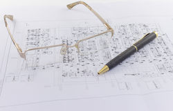 Glasses and pen lie on the engineering drawing Royalty Free Stock Images