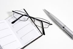Glasses, pen and notebook Stock Image