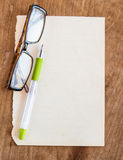 Glasses and pen on old paper Royalty Free Stock Image