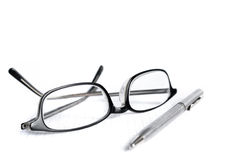 Glasses and pen on paper Royalty Free Stock Photos