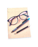 Glasses, pen and pencil put on brown paper. Royalty Free Stock Photography