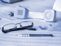 Glasses, pen and phone on financial documents Stock Photography