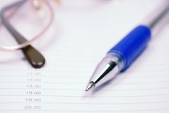 Glasses and pen on planner Royalty Free Stock Image