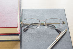 Glasses and Pen put on notebook Royalty Free Stock Photos