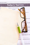 Glasses and pen on salary survey from Stock Images