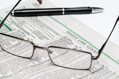 Glasses and a pen on a stock section of The Wall Street Journalfor editorial use only Royalty Free Stock Images
