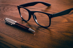 Glasses with pen and tablet on a wooden natural table. Home office. Concept of work in a office and accessories. Glasses with pen and tablet on a wooden natural stock images