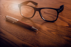 Glasses with pen and tablet on a wooden natural table. Home office. Concept of work in a office and accessories. Glasses with pen and tablet on a wooden natural royalty free stock images