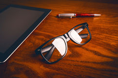 Glasses with pen and tablet on a wooden natural table. Home office. Concept of work in a office and accessories. Glasses with pen and tablet on a wooden natural royalty free stock image