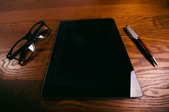 Glasses with pen and tablet on a wooden natural table. Home office. Concept of work in a office and accessories. Glasses with pen and tablet on a wooden natural stock photography
