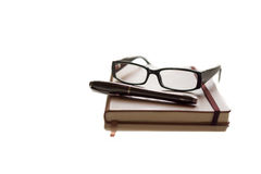 Glasses and pen on top of brown agenda. With white background Stock Photos