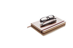 Glasses and pen on top of brown agenda on white background. Glasses and pen on top of brown agenda with white background Royalty Free Stock Photos