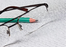 Glasses and  pencil. On the background of a binary code Stock Photography