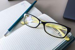Glasses and a pencil are on the notebook. Free space. Education. Business stock photography