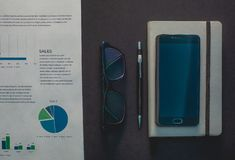 Glasses and phone lie on a black background next to a gray notepad stock photos