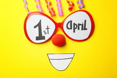 Glasses with phrase. `1st April`, clown nose and streamers on color background. Fool`s day composition Royalty Free Stock Photo
