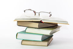 Glasses on a pile of books. On a white background Royalty Free Stock Image