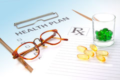 Glasses and pill capsules on health plan notes. Or patient record form Stock Images