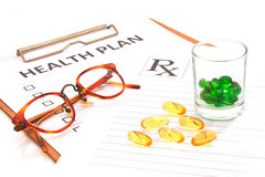 Glasses and pill capsules resting on health plan notes Stock Images
