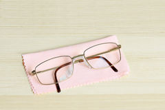 Glasses with pink cleaning cloth on a table top Royalty Free Stock Photo