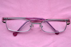 Glasses. Pink metallic children glasses on pink background Stock Photography