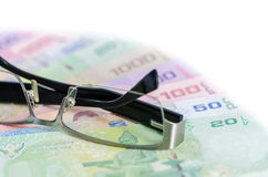 Glasses is place on thai baht banknote. (Business royalty free stock photos