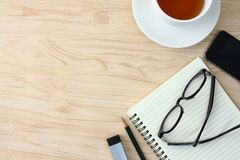 Glasses placed on the notebook. There are phones and coffee mugs and space for writing text. stock photo