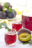 Glasses of plum alcohol and fresh plums Royalty Free Stock Photography