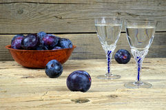 Glasses of plum brandy with plums Stock Photos