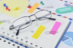 Glasses with post It notes and pin on business diary page Royalty Free Stock Photography