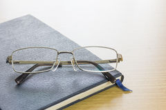 Glasses put on text book Stock Image