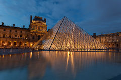 Glasses pyramid in Louvre Museum. At twilight time Stock Photos