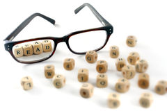Glasses and read message written in wooden blocks, isolated. On white background, some blurry letters around, symbol, concept Stock Photo