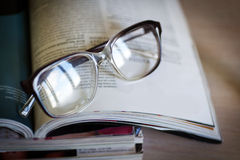 Glasses for reading on a magazines Royalty Free Stock Photography