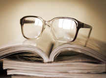 Glasses for reading on a stack of magazines, in soft focus Stock Image