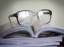 Glasses for reading on a stack of magazines, in soft focus Royalty Free Stock Photos