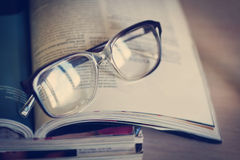 Glasses for reading on a stack of magazines, in soft focus Stock Images