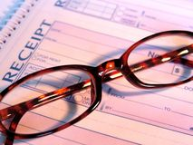 Glasses and Receipt. A pair of tortoise shell reading glasses on a receipt book Stock Photos