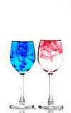 Glasses red and blue ink. Two wine glasses filled with water and spreading red and blue ink Stock Photography