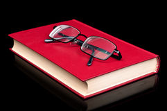 Glasses and red book. Isolated on a black background Stock Images