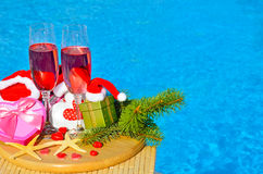 Glasses with red champagne  and Christmas decor on swimming pool Stock Photo