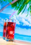 Glasses of red cocktail with blur beach and palm Stock Photography