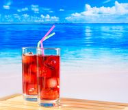 Glasses of red cocktail with blur beach Royalty Free Stock Images