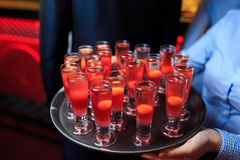 Glasses with red cocktails on a tray in the hands of the waiter. Side view Royalty Free Stock Image